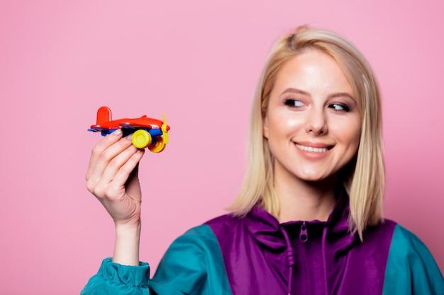 Frau mit spielzeugflugzeug, das vom urlaub auf rosa wand träumt