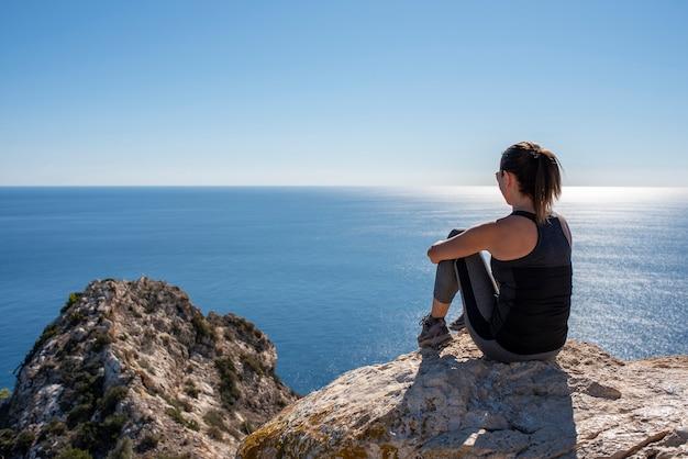 Frau mit sportbekleidung, die auf einigen felsen sitzt und die landschaft des mittelmeers beobachtet