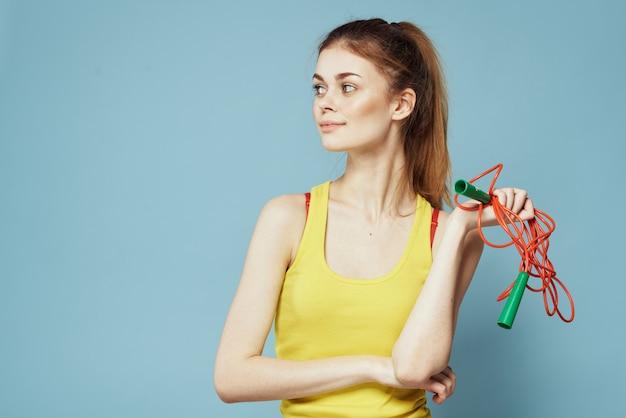 Frau mit springseil sportübung gelben tank top blauen hintergrund.