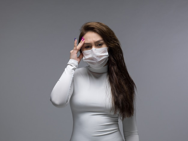 Frau mit starken kopfschmerzen in der weißen schutzmaske