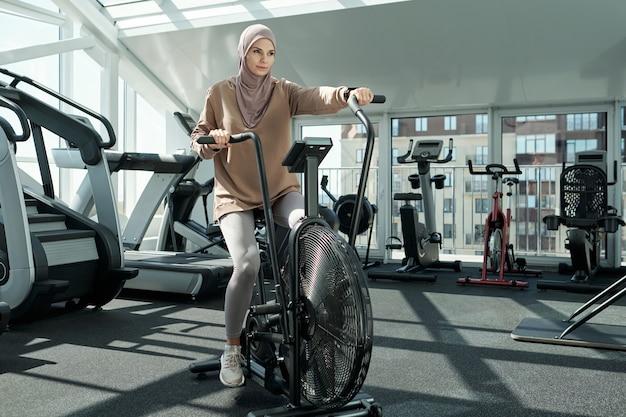 Frau mit stationärem fahrrad