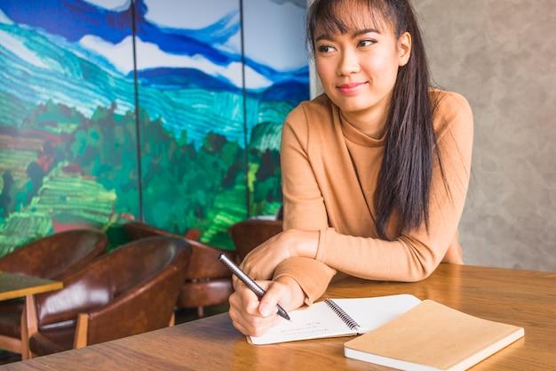 Frau mit stift und notizbüchern