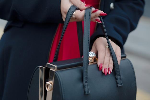 Frau mit stilvollem blauem mantel, der schwarze ledertasche öffnet. platz für text