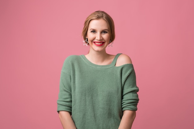Frau mit stilvollem make-up, roten lippen, grünem pullover, der auf rosa aufwirft