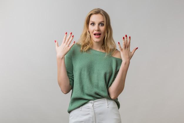 Frau mit stilvollem make-up und grünem pullover, der auf rosa aufwirft