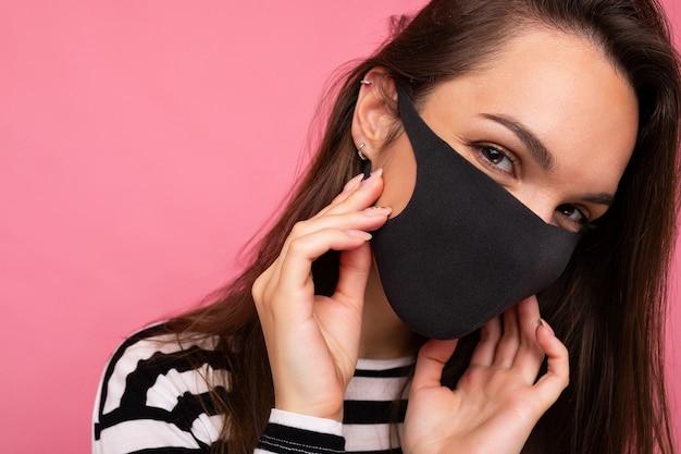 Frau mit stilvoller gesichtsschutzmaske, die auf rosafarbenem hintergrund posiert. trendiges modeaccessoire während der quarantäne der coronavirus-pandemie. studioportrait hautnah. kopieren, leerer platz für text