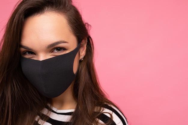 Frau mit stilvoller gesichtsschutzmaske posiert auf rosafarbenem hintergrund trendiges modeaccessoire während