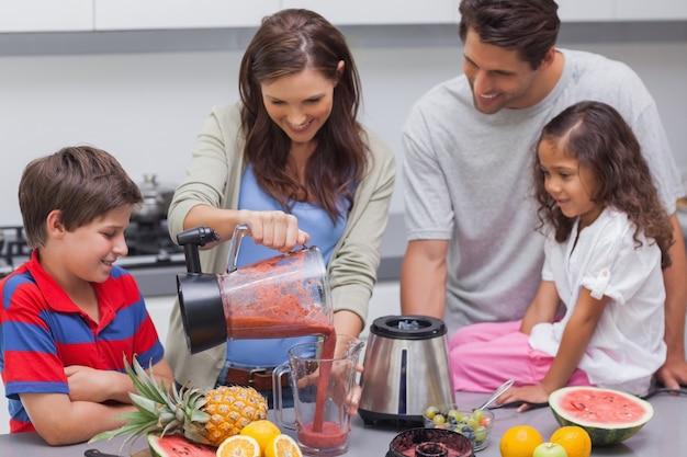 Frau mit strömender frucht der familie von einer mischmaschine