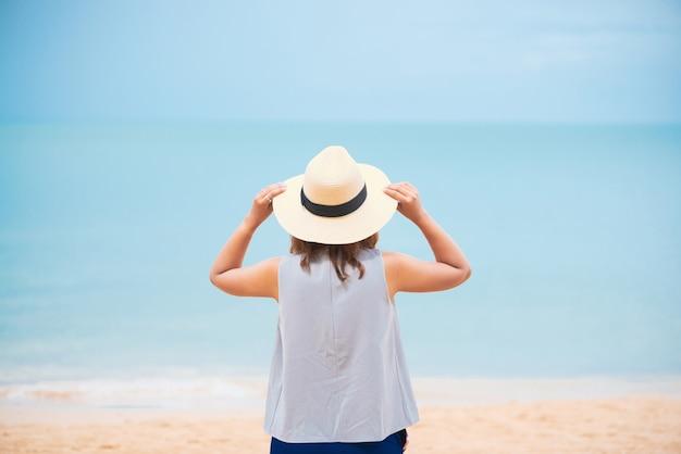 Frau mit strohhut am strand entspannen