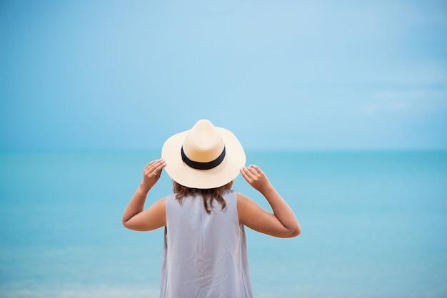 Frau mit strohhut am strand entspannen.