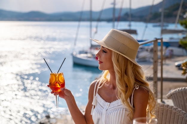 Frau mit strohhut trinkt aperol-spritz-cocktail auf der sommercafé-terrasse