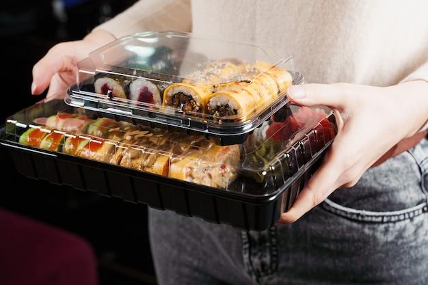 Frau mit sushi-set-box auf schwarzem hintergrund