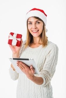 Frau mit Tablet und Geschenkbox