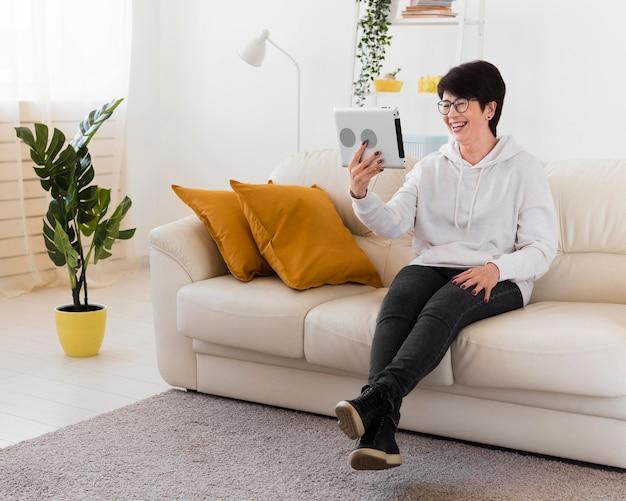 Frau mit tablette auf sofa