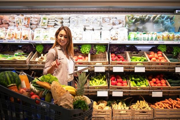 Frau mit tablette, die einkaufswagen prüft, um zu sehen, ob sie alles hat, das sie zum mittagessen benötigt