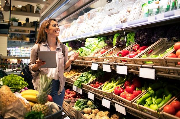 Frau mit tablette, die gesundes essen im supermarktlebensmittelgeschäft kauft