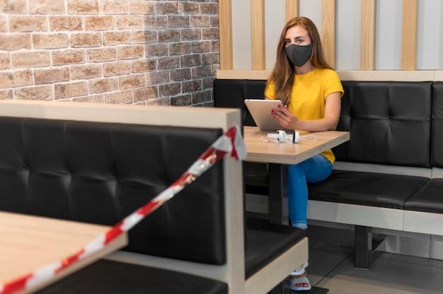 Frau mit tablette, die maske trägt, die neue maßnahmen an der terrasse respektiert
