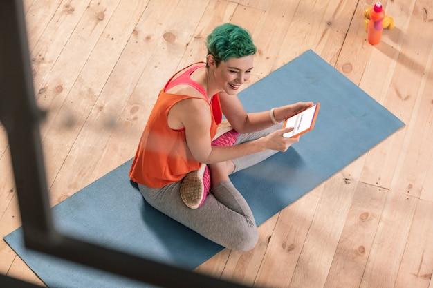Frau mit tablette. grünhaarige frau in sportkleidung sitzt auf sportmatte und benutzt tablet