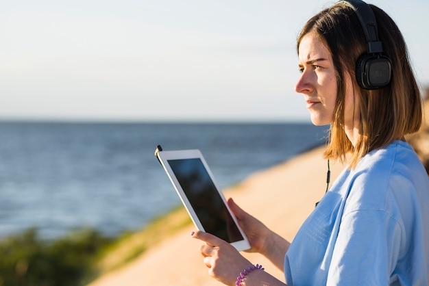 Frau mit tablette nahe meer