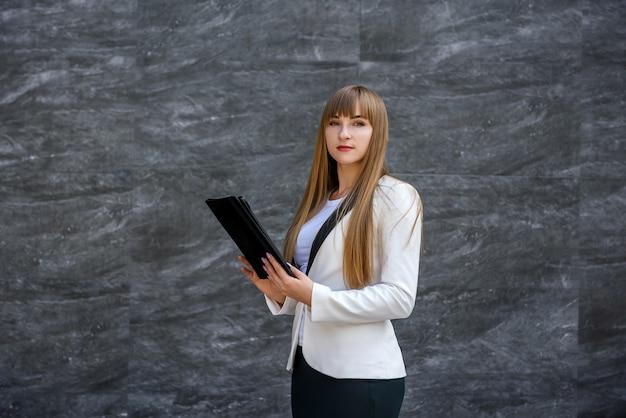 Frau mit tablette. schöne geschäftsfrau, die gerät auf abstraktem hintergrund hält