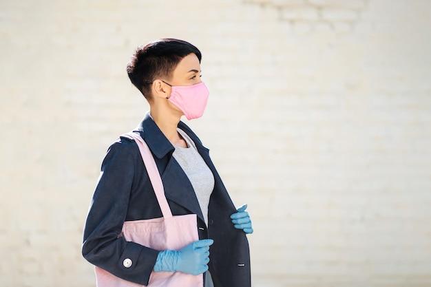 Frau mit tasche geht einkaufen. frauen, die während des ausbruchs von covid 19 baumwollmaske und handschuhe auf der straße tragen. schutz in der prävention des coronavirus.