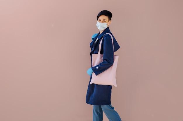 Frau mit tasche geht einkaufen. frauen, die während des ausbruchs von covid 19 medizinische maske und handschuhe auf der straße tragen. schutz in der prävention des coronavirus.