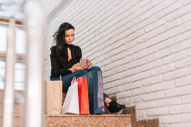Frau mit taschen unter verwendung des telefons auf schritten