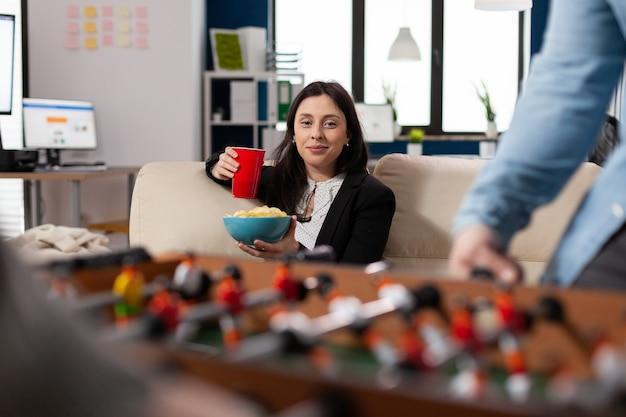 Frau mit tasse alkohol am tischkicker nach der arbeit