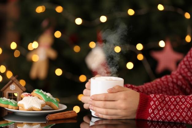 Frau mit tasse des köstlichen heißen kakaos und der weihnachtsplätzchen, die am tisch sitzen