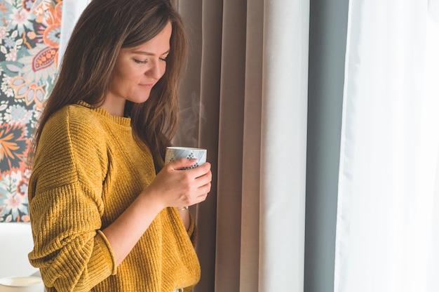 Frau mit tasse heißem getränk durch das fenster. fenster betrachten und tee trinken. guten morgen mit tee. herbst winter zeit