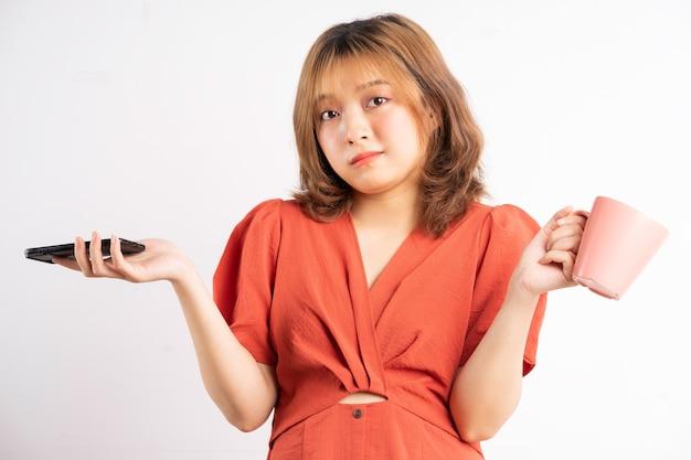 Frau mit tasse wasser und telefon mit ausdruck im hintergrund