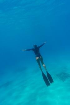 Frau mit tauchausrüstung, die im ozean schwimmt