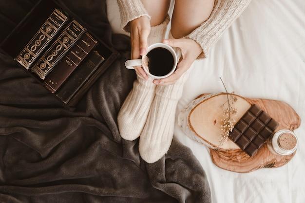 Frau mit tee in der nähe von büchern und schokolade