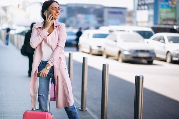 Frau mit telefon am flughafen