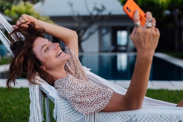 Frau mit telefon, das auf hängematte mit handy liegt