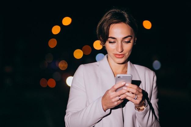 Frau mit telefon draußen in der nachtstraße