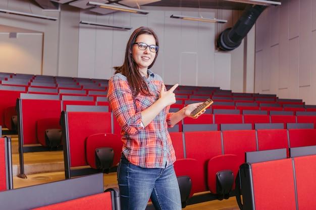 Frau mit telefon im amphitheater der universität