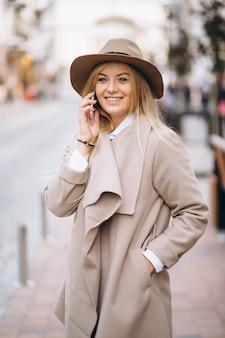 Frau mit telefon im hut außerhalb der straße
