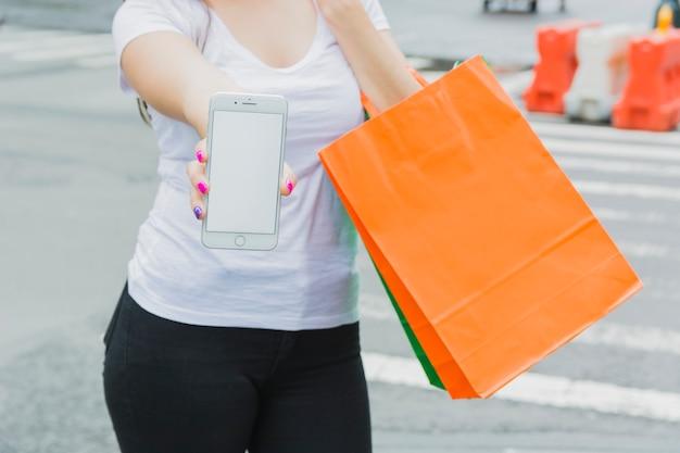 Frau mit telefon und einkaufstaschen