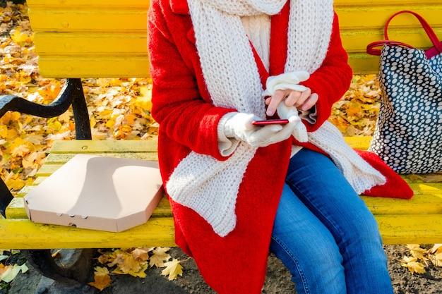 Frau mit telefon und kasten für pizza, die auf einer gelben bank im herbstpark sitzt. liefer- oder mitnahmekonzept.