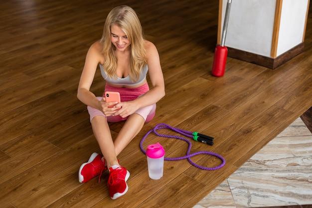 Frau mit telefon und springseil
