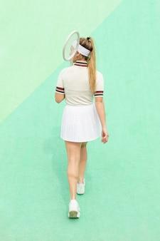 Frau mit tennisschläger von hinten