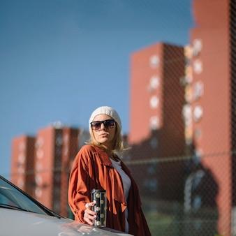 Frau mit thermosflasche in der nähe von auto