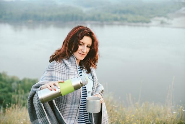 Frau mit thermoskanne gießt heißen tee in becher auf wiese gegen fluss