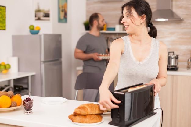 Frau mit toaster zum braten von brot in der küche während des frühstücks. junge hausfrau zu hause, die morgenmahlzeit kocht, fröhlich mit zuneigung und liebe