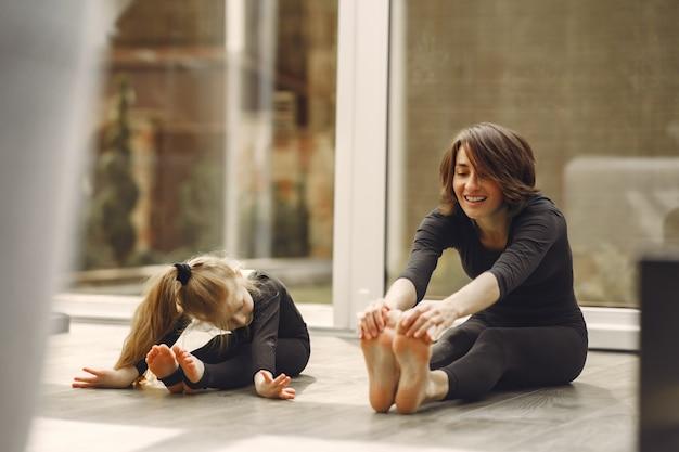 Frau mit tochter ist in der gymnastik beschäftigt