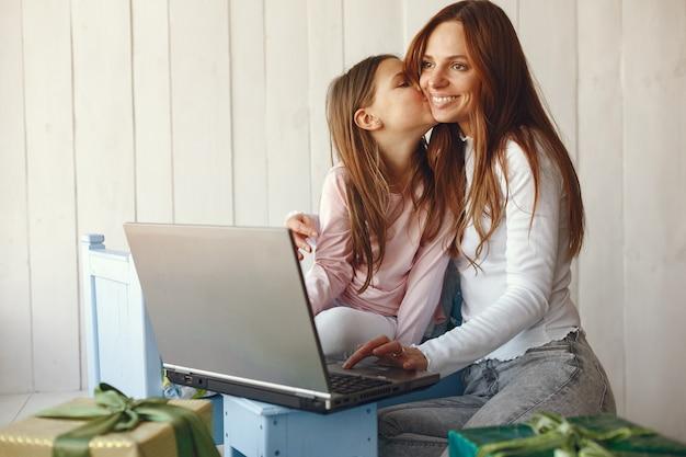 Frau mit tochter mit laptop-computer