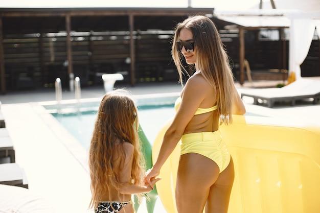 Frau mit tochterionenurlaub. sie werden in einem pool mit einer aufblasbaren matratze in ananasform schwimmen.