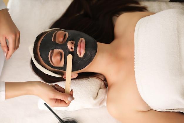 Frau mit ton gesichtsmaske von kosmetikerin anwenden.