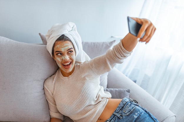 Frau mit tonmaske, die selfie mit handy zu hause nimmt, das entspannung genießt